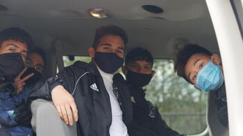 a group of boys posing for the camera, all wearing masks