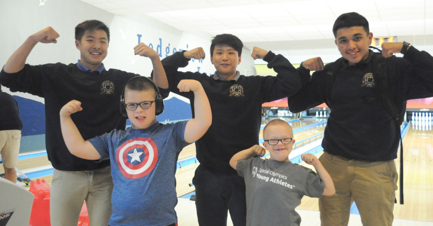 a group of boys posing together at a bowling alley