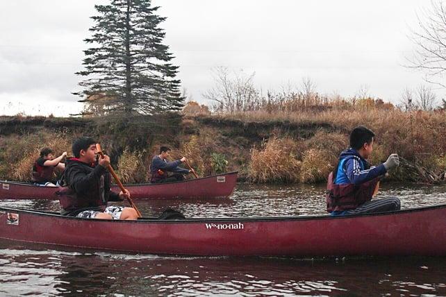 boys rowing in a canoe