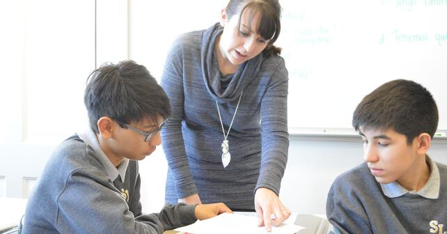 a teacher helping two students with their work