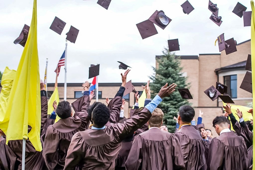 boys throwing graduation caps